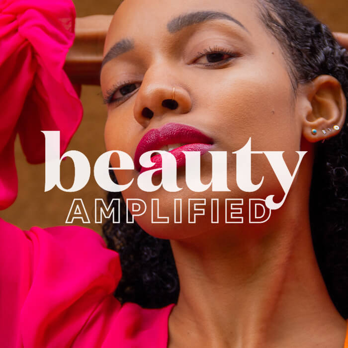 """Close-up image of a Black model posing with white, super imposed text """"beauty amplified"""""""
