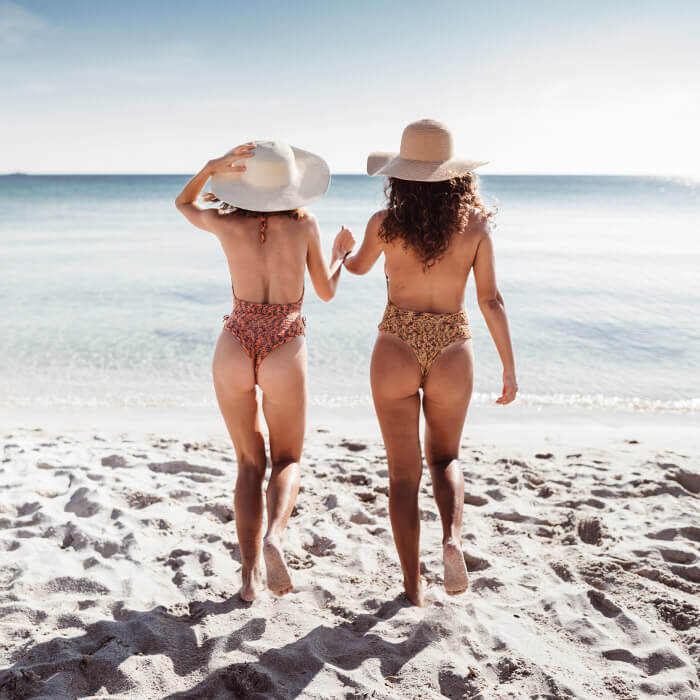 Two women in their swimsuits and straw hats on the beach