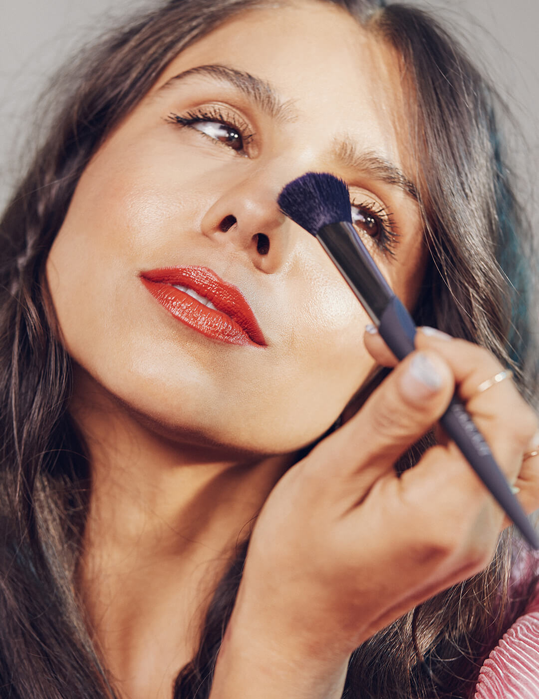 An image of a model touching her nose with a makeup brush