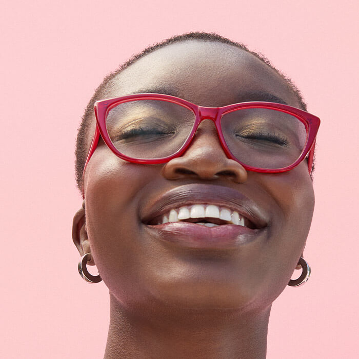 Close-up image of a model with very short hair wearing red frame eyeglasses smiling with eyes closed