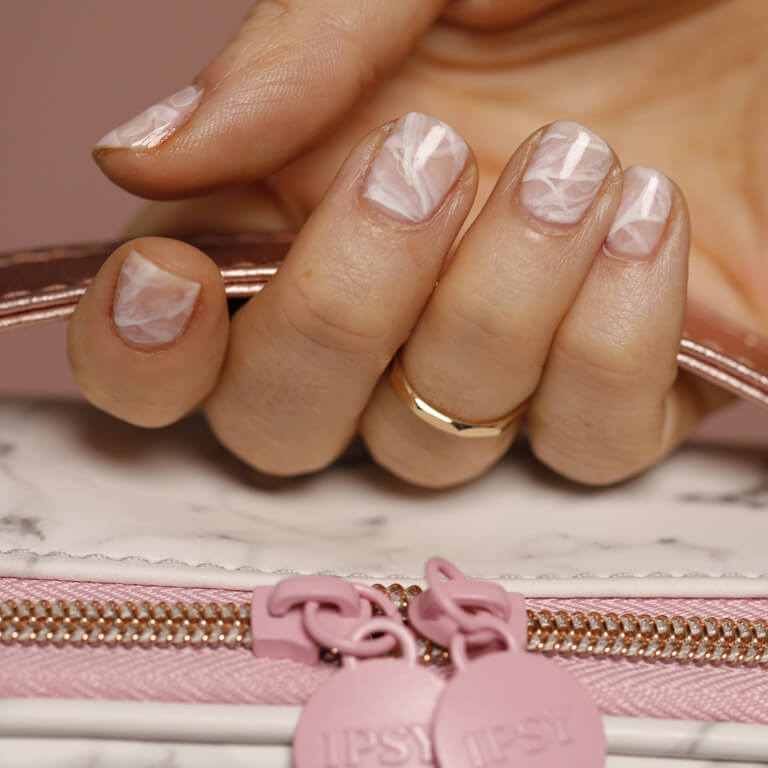 A close-up of a pink marble manicure.
