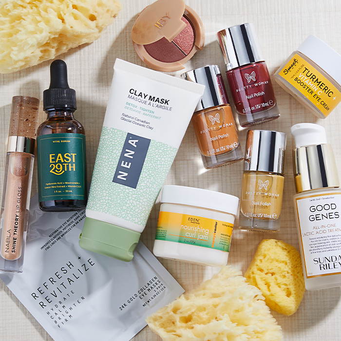 Clean beauty products from various brands scattered on light brown textile together with yellow sponges