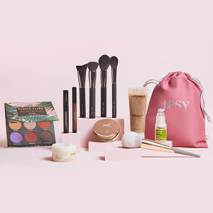Image of makeup and skincare products, makeup brushes, and IPSY drawstring bag on light pink background