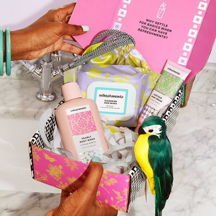 Close-up image of a woman's hands holding a pink box full of skincare products with a green toy bird