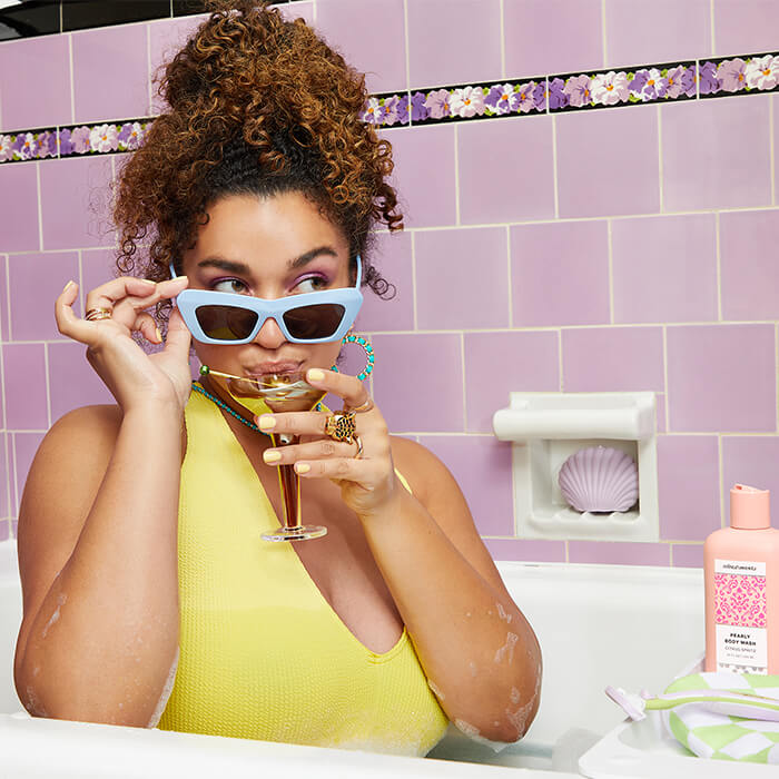 Curly-haired model in a yellow dress holding her light blue sunglasses and sipping a glass of cocktail in a bathtub with REFRESHMENTS body care products