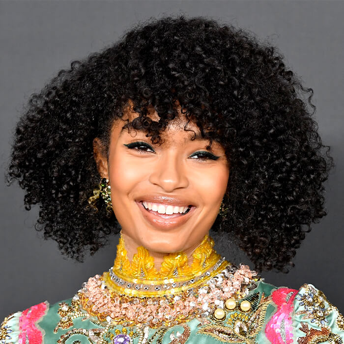 Yara Shahidi looking glam in a colorful dress and bold eyeliner makeup look paired with nude lips