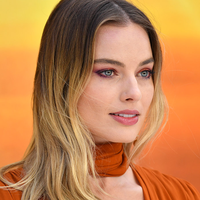 A photo of Margot Robbie with blonde hair and shadowed roots