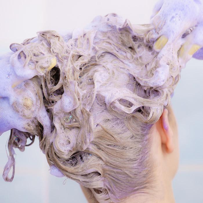 A photo of a woman applying purple shampoo on her hair