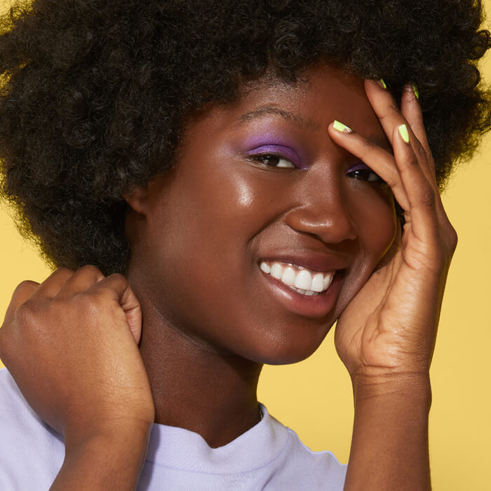 Black model rocking a purple eyeshadow look and lime green nails smiling and covering one eye with her hand