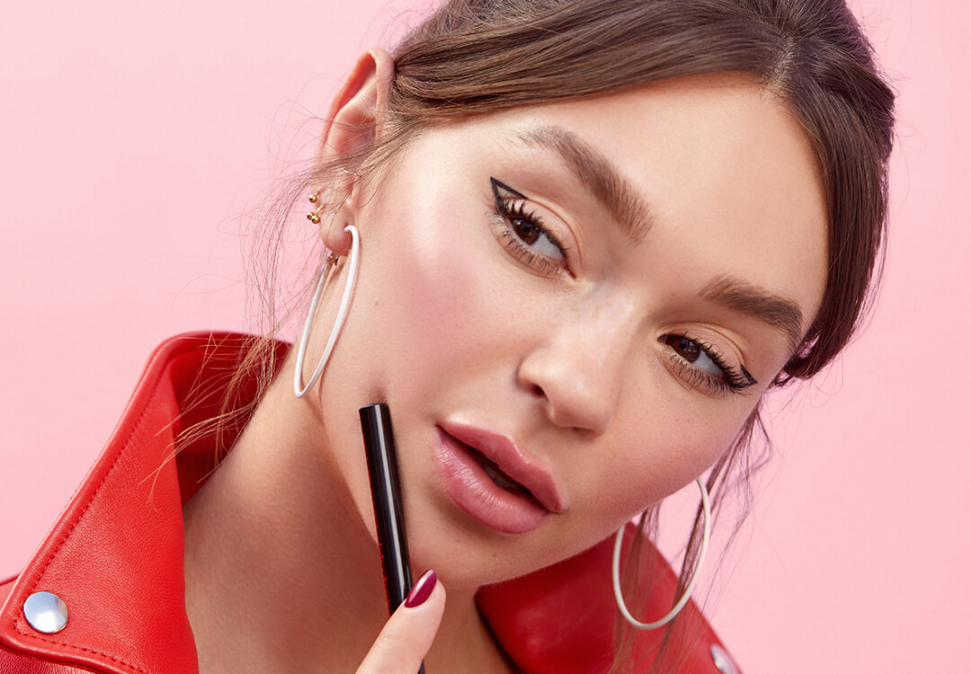 An image of a model in a bold red top wearing a negative space eyeliner look paired with a nude pink lipstick and big hoop earrings