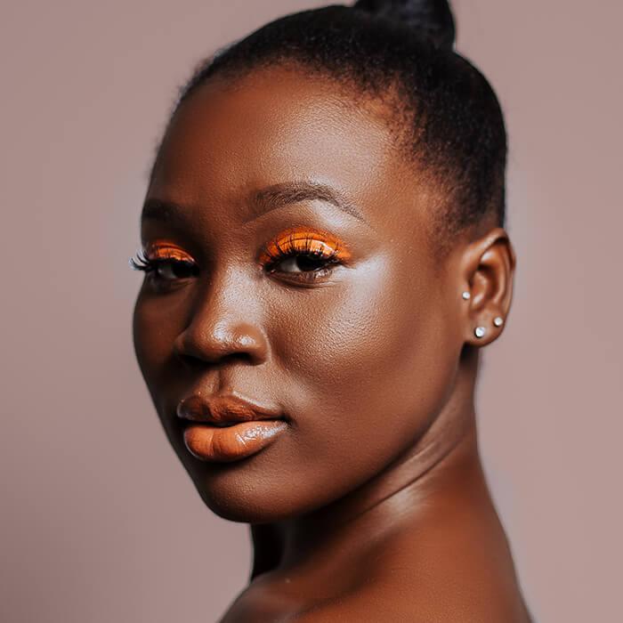 Beauty portrait of a Black woman rocking an orange eyeshadow makeup look