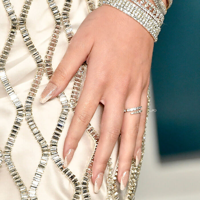 Close-up of Hailee Steinfeld's hand with silver bracelets and rings, and glittery French tip nail art resting on bejewelled cream dress