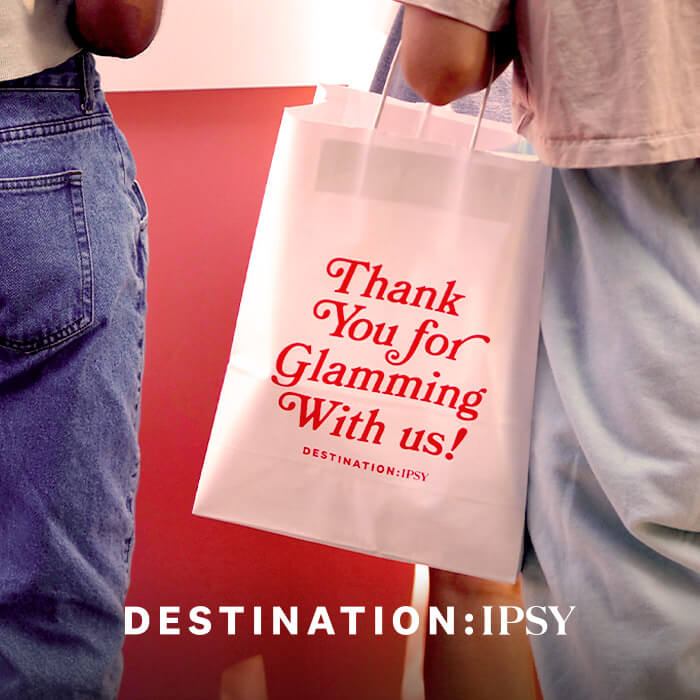 """Close-up of two women with a white paper bag with red text """"Thank You for Glamming With us!"""" and white text """"DESTINATION: IPSY"""""""