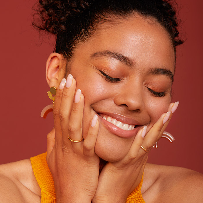A photo of a young woman smiling holding her face with her hands