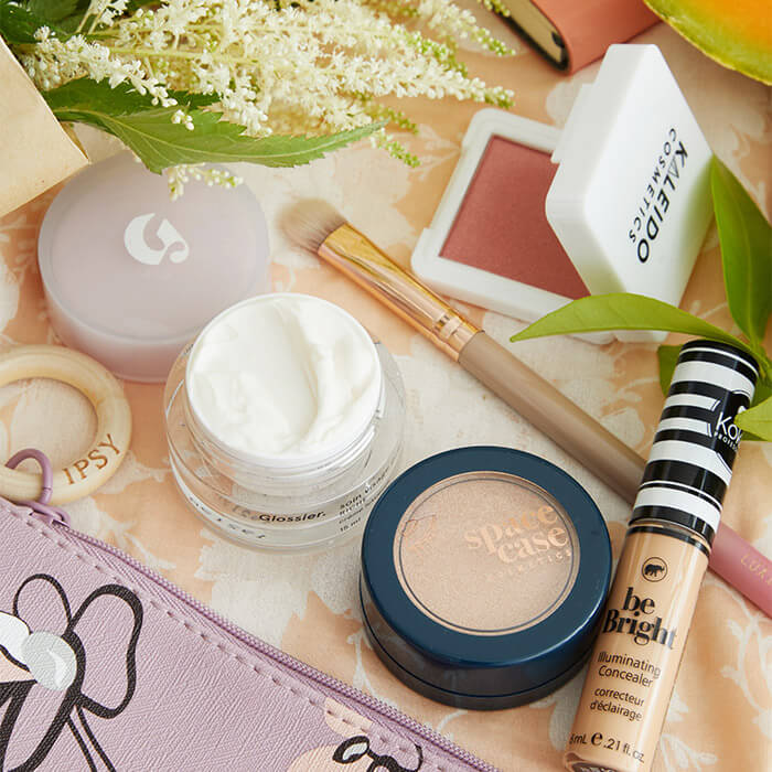 Flat-lay image of IPSY April 2020 Glam Bag, skincare, and makeup products and tools on top of floral patterned textile