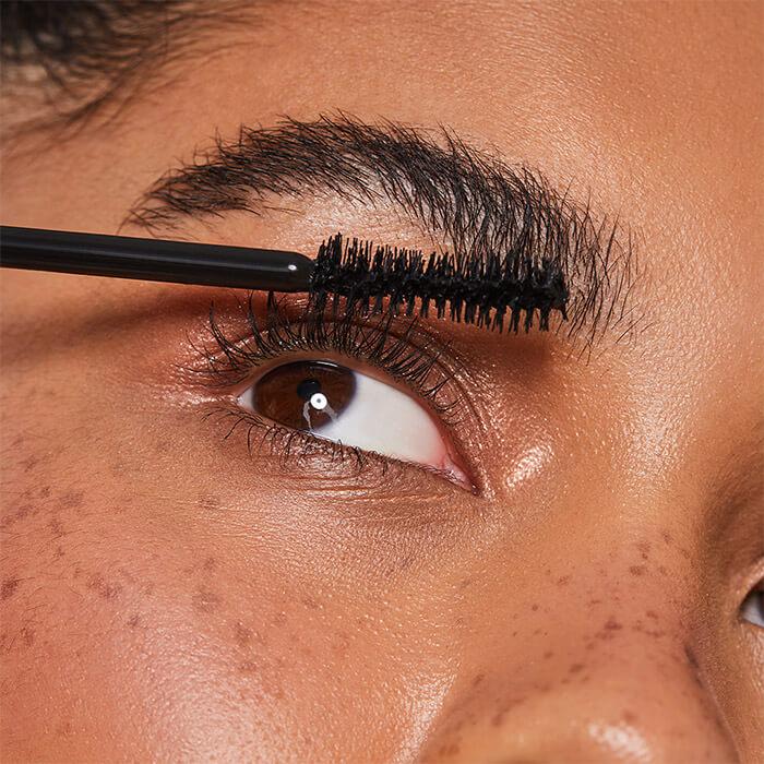 Close-up image of a woman applying mascara to her eyelashes