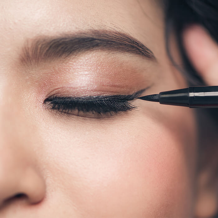 Close-up image of a woman with a neutral eyeshadow look applying liquid eyeliner