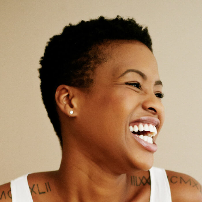 Side profile image of a black woman with short hair in a white tank top laughing