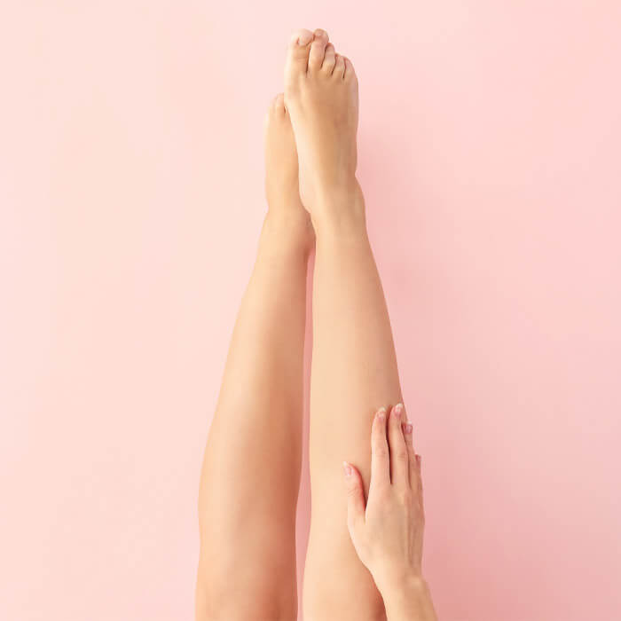 Woman's smooth legs and right hand on pink background