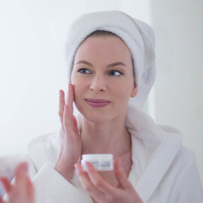 Mature woman in bathrobe putting on face cream in front of the mirror