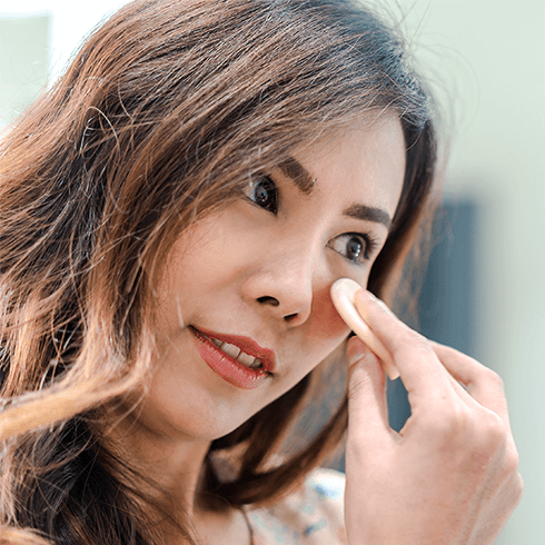 Close-up of a young woman applying face makeup using a sponge