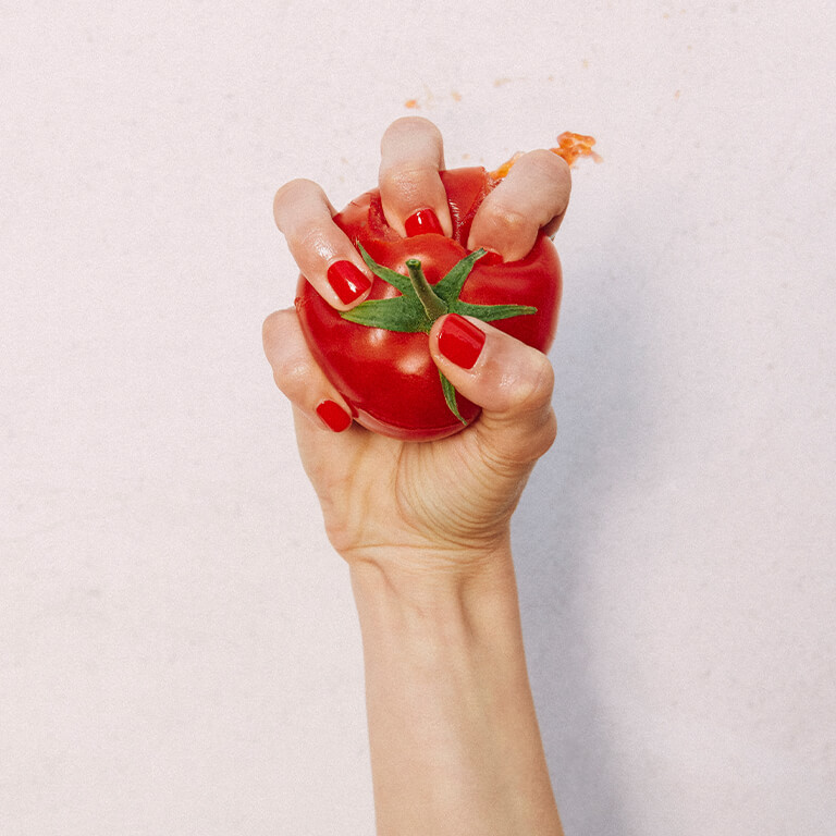An image of a hand with bright red mani crushing a tomato