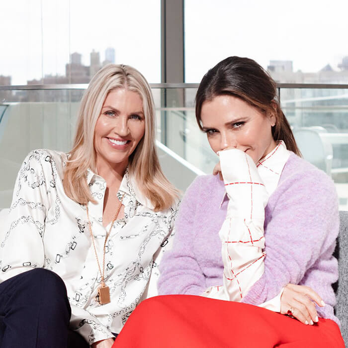 Sarah Creal and Victoria Beckham smiling and posing on a grey couch in an apartment