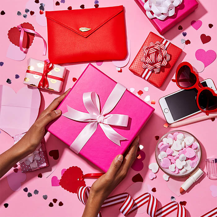 Image of a woman's hands holding a big pink gift box, small red and white gift boxes, heart-shaped confetti, bowl of heart-shaped candies, iPhone, red-framed heart sunglasses, and pink pen scattered on pink background