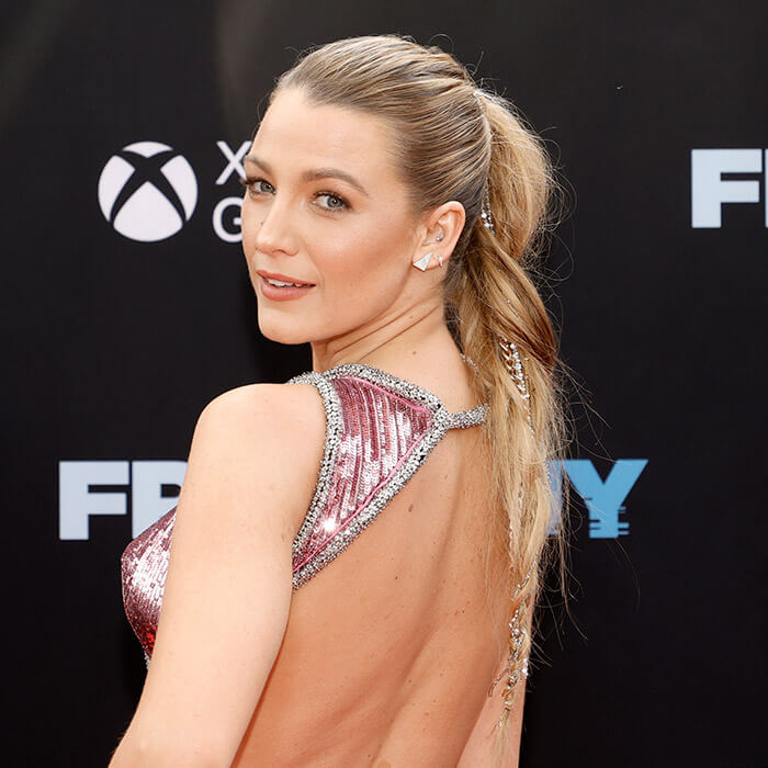 Close-up of Blake Lively posing and rocking a ponytail hairstyle embellished with gold and silver chains on the red carpet