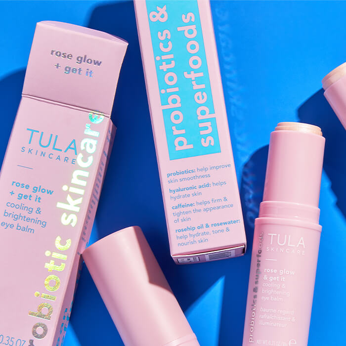 Tubes and boxes of TULA Rose Glow & Get It Cooling & Brightening Eye Balm on blue background