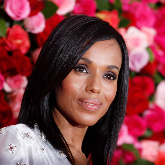 Glam Kerry Washington smirking against pink and red roses background