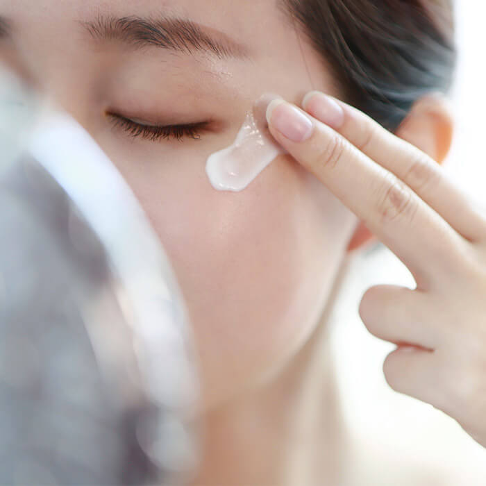 Image of a woman partly covered by her mirror putting on eye cream