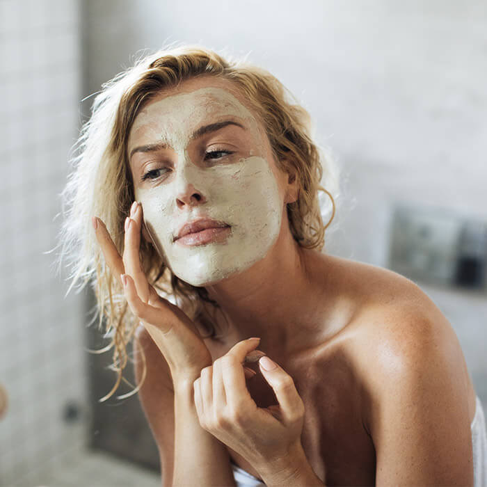 Image of a woman applying face mask in her bathroom