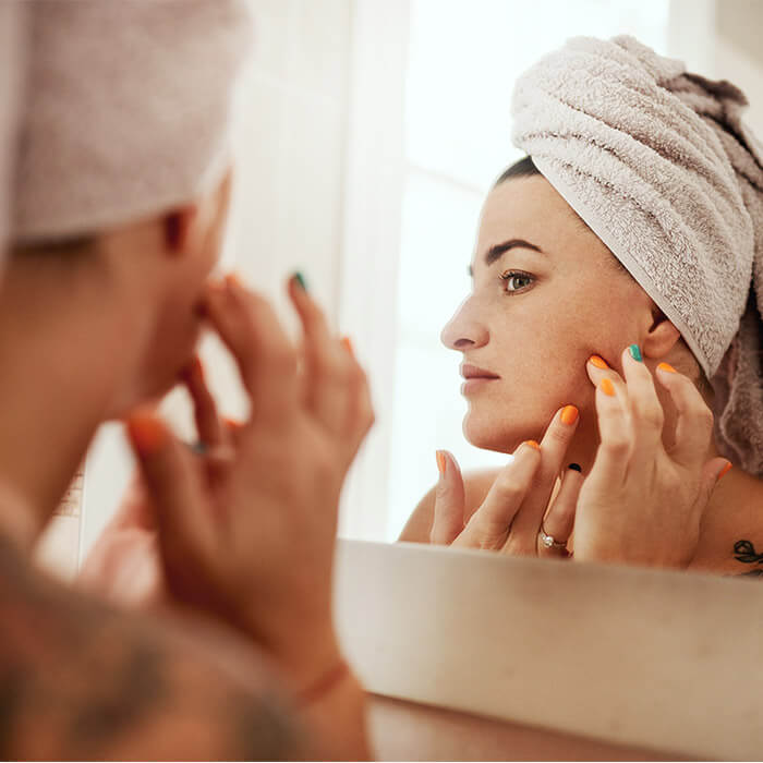Image of a woman with hair wrapped in a towel checking a zit in the mirror
