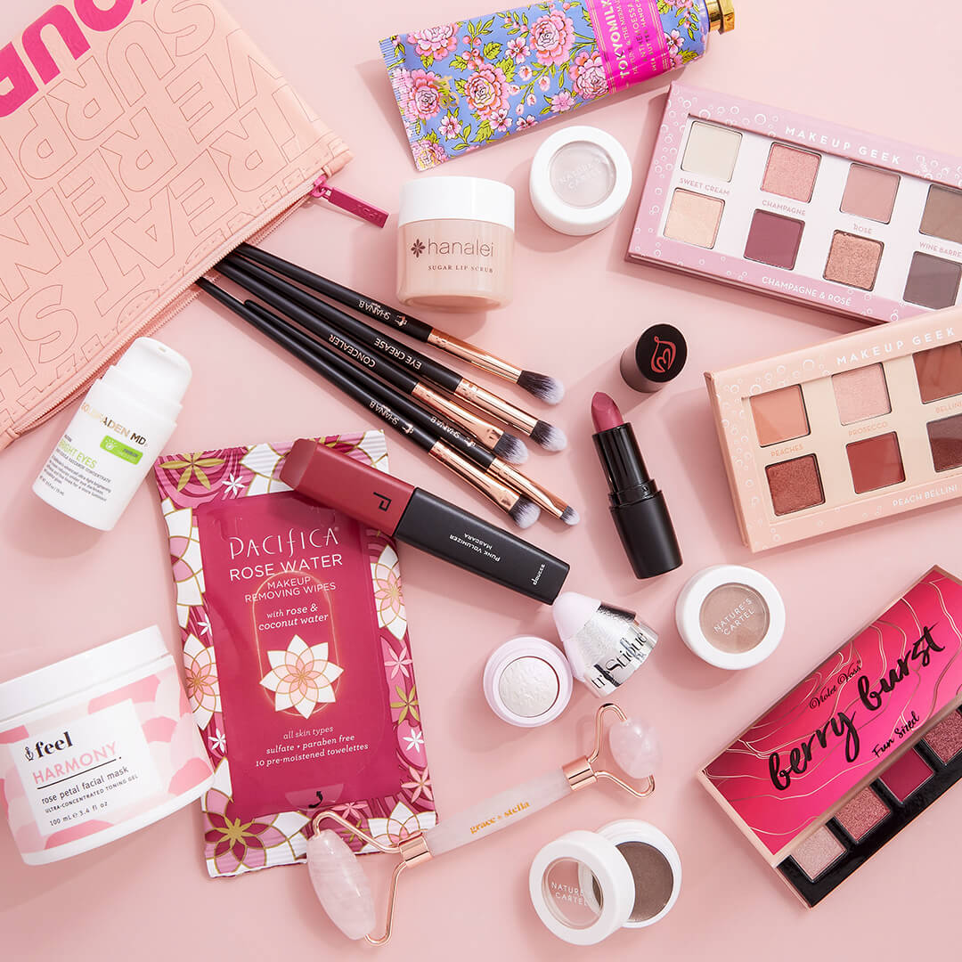 Flat lay image of makeup and skincare products and tools and a makeup pouch on a light pink surface