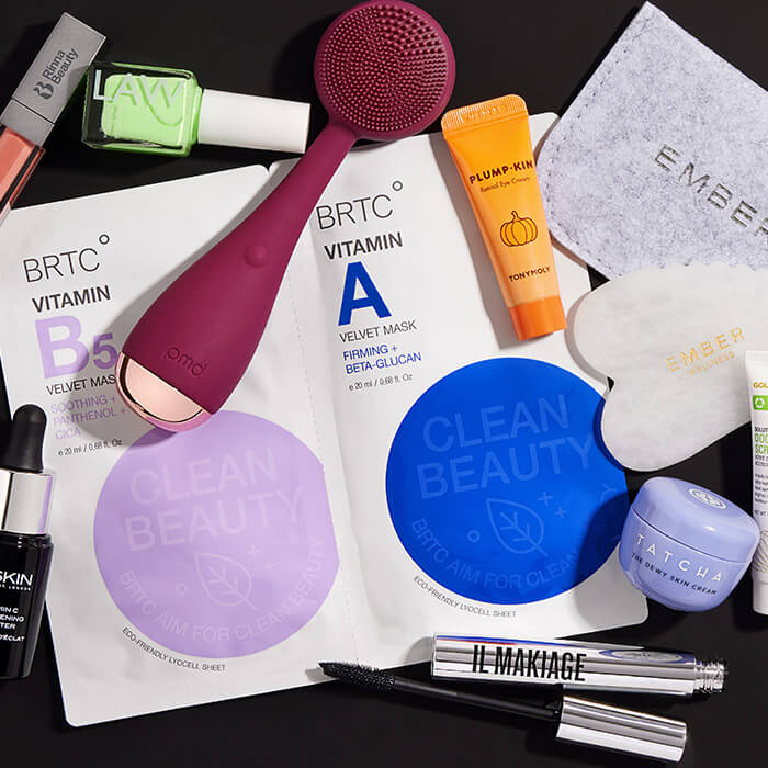 Makeup, and skincare products and tools scattered on black background