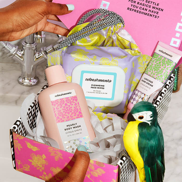 Image of a woman's hand touching a Refreshments membership box full of personal care products on a marble surface