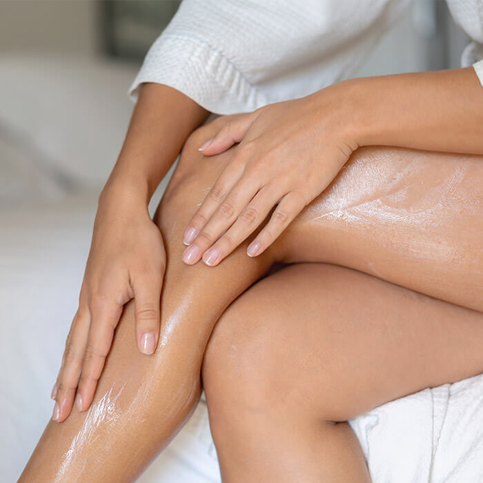 Close-up on a woman applying lotion on her legs