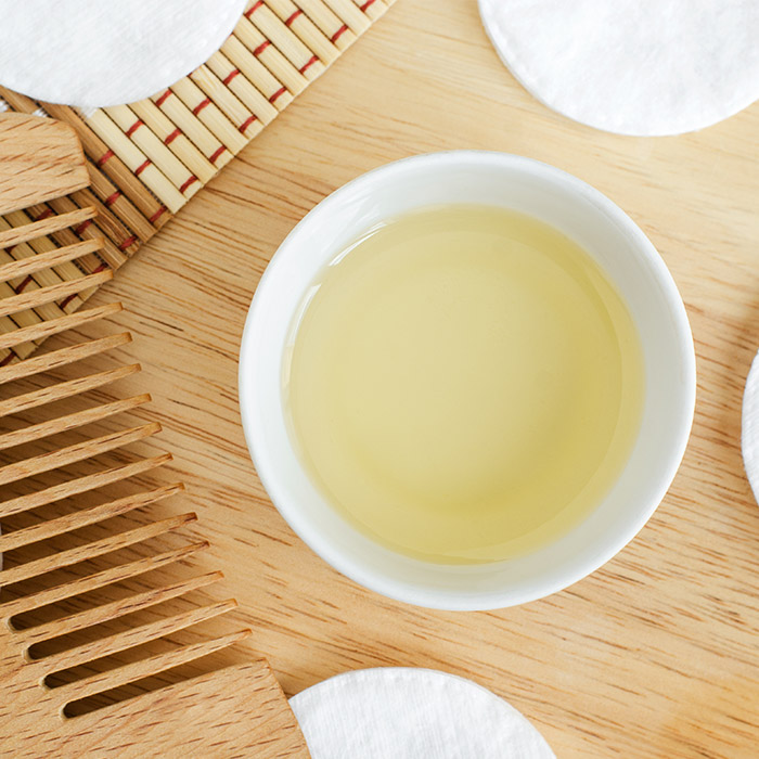 Flat lay image of a bowl of oil, wooden comb, and cotton pads on wooden surface