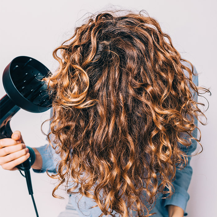 A photo of a woman sitting on chair styling her curly hair with a diffuser
