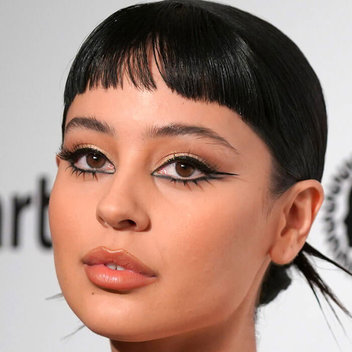 Close-up of Alexa Demie rocking short bangs and a graphic eyeliner makeup look