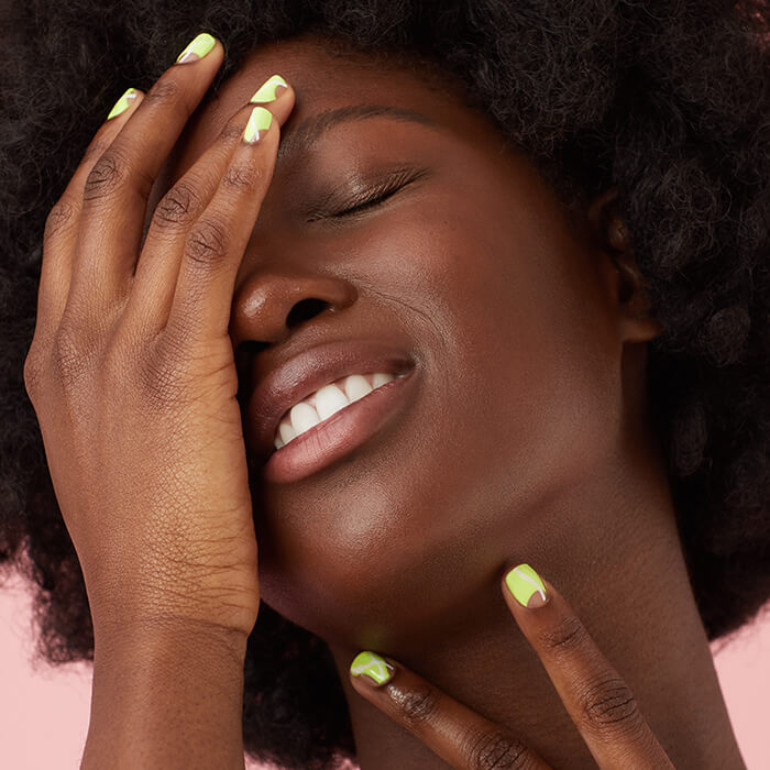 Close-up of a Black model with clear skin posing with her hands with lime green abstract nail art on pink background