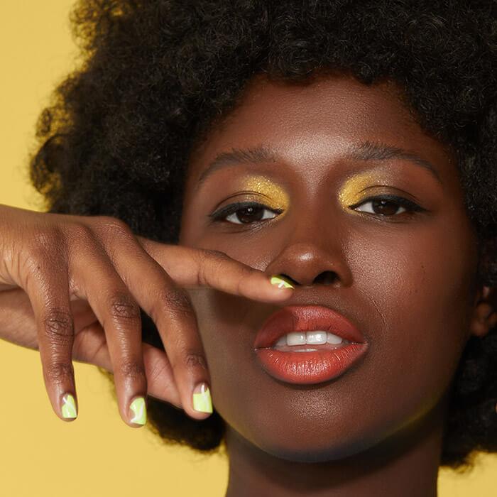 Close-up of a Black model rocking a yellow gold eye makeup look and slime yellow nail polish