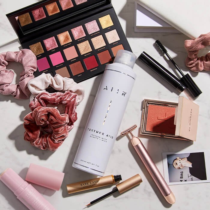 Flat lay image of makeup, skincare, and hair care products and tools on white marble surface