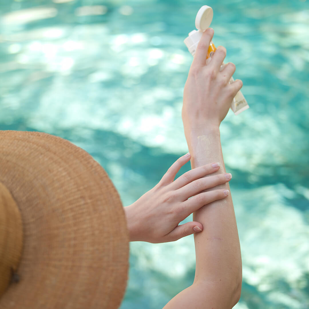 Image of a woman applying sunscreen to her arm.