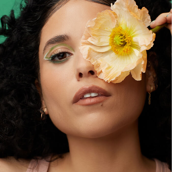 Close-up of a model rocking a green eyeshadow and white eyeliner makeup look with a yellow flower covering her other eye