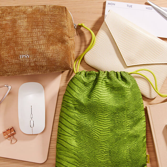 Flat lay image of the August 2021 IPSY Glam Bag, Glam Bag Plus, and Glam Bag X bags, wireless mouse, eyeglasses, notebooks, scissors, paper clips, and calendar notes on a table top