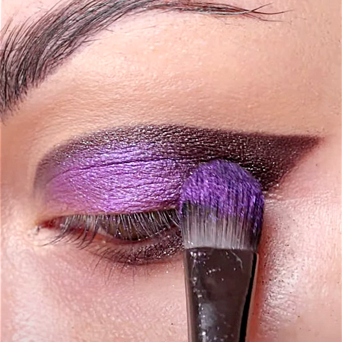 Close-up image of Bailey Sarian applying purple eyeshadow on her eye with a brush