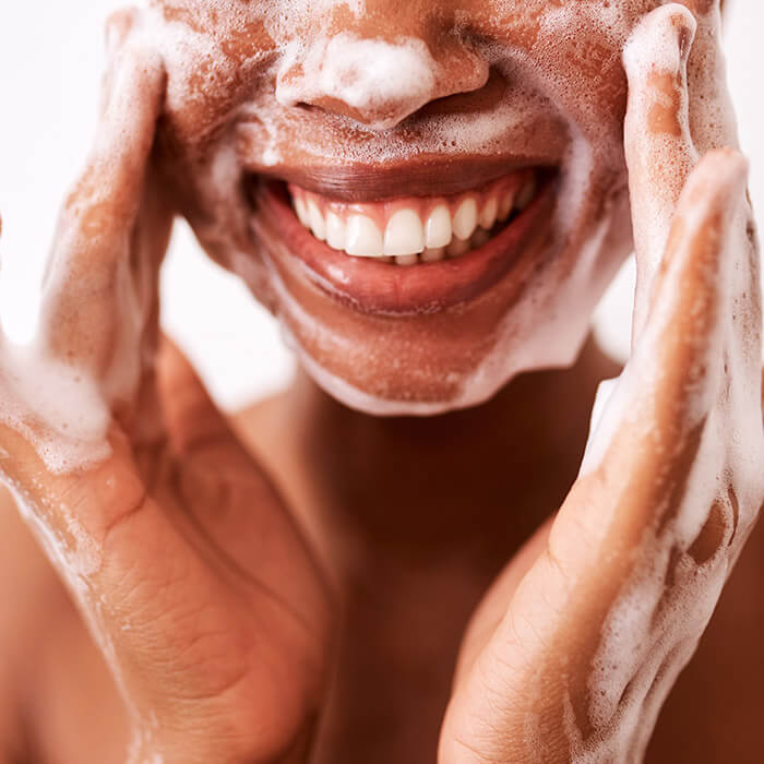 Close-up of a smiling woman washing her face with foam cleanser