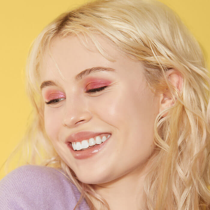 Close-up of a model smiling and rocking a bright pink eyeshadow makeup look